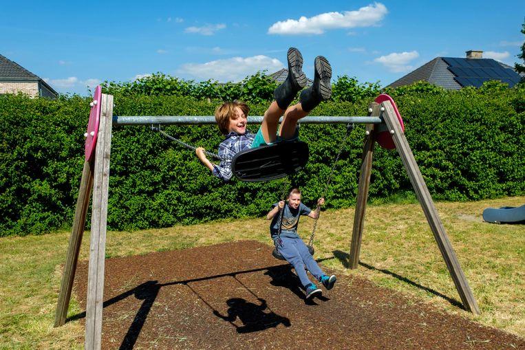 Broers Logan (blauw hemd, 9 jaar) en Angelo (rode t-shirt, 7) spelen samen met Dante (12) op de heropende speeltuin op het Toebenteplein in Niel.