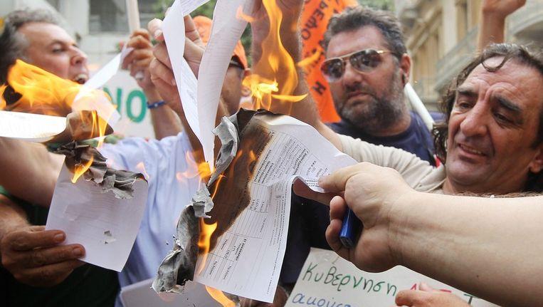 Ambtenaren verbranden aanslagen voor extra inkomsten belasting op de stoep van het ministerie van Financiën in Athene. © EPA Beeld null