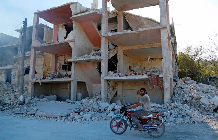 Een man rijdt op een motor langs de verwoeste gebouwen in Jisr al-Shughur in Idlib.