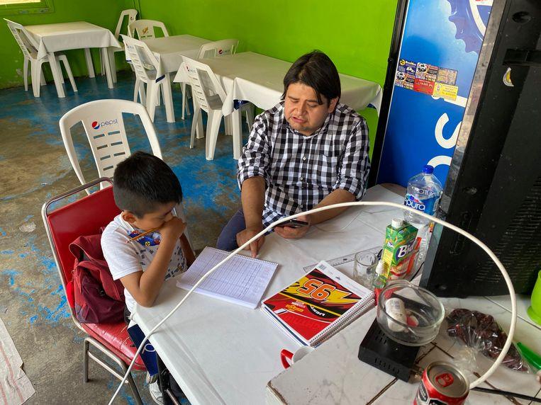 Ciro Nataren helpt zijn zoontje Alan met huiswerk in Mexico-Stad. Beeld Jan-Albert Hootsen