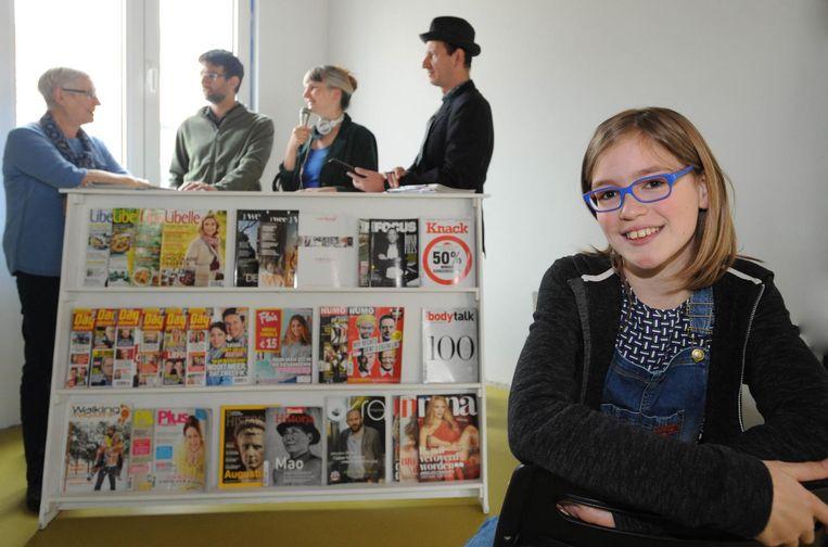 Pieternel Maes (12) met op de achtergrond enkele acteurs bij een decorstuk uit het theaterstuk. Het verhaal speelt zich af in een krantenwinkel.