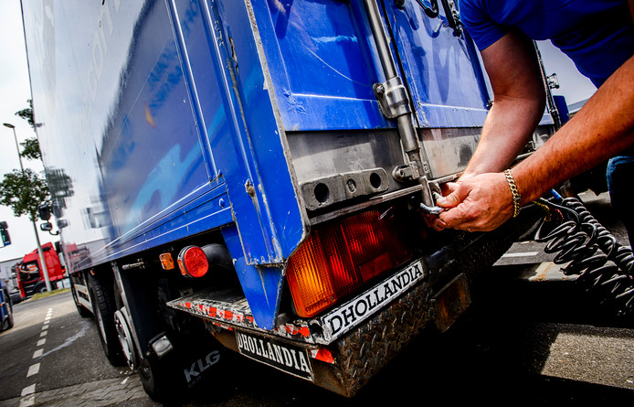 Een vrachtwagenchauffeur vergrendelt zijn vrachtwagen met een extra slot
