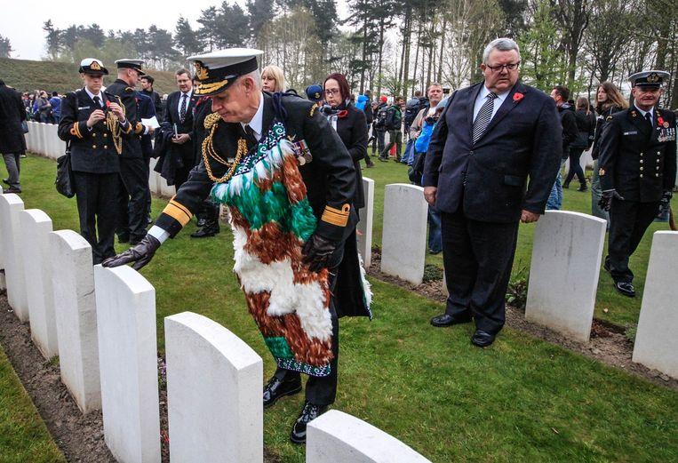 Een Nieuw-Zeelandse militair met een Maori-mantel brengt hulde aan één van de graven.