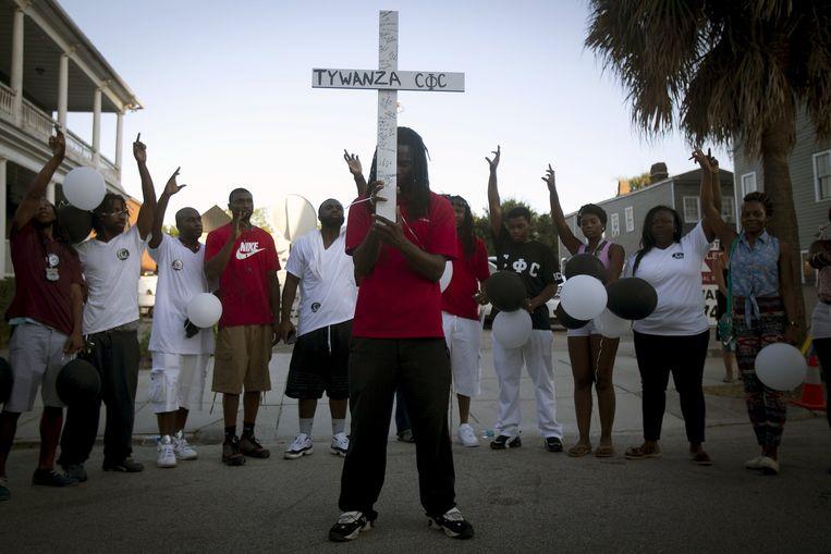 Mensen bidden voor de Emanuel-kerk in Charleston. Beeld reuters