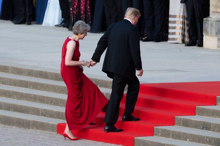 Donald Trump begeleidt Theresa May over de rode loper naar het Blenheim Palace, waar een diner op het programma stond. Beeld AP
