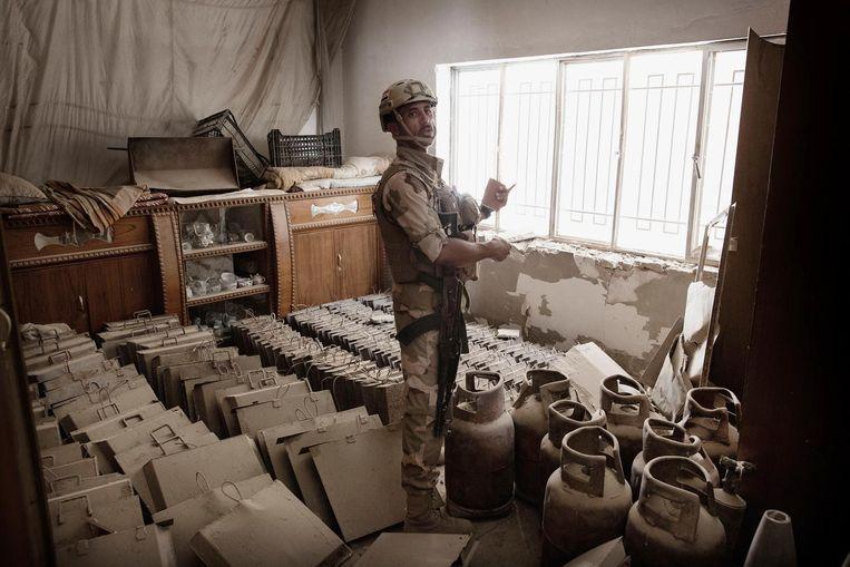 Een Iraakse militair inspecteert in Falluja een kamer waar de extremisten van IS volgens het leger een bommenfabriek hadden gevestigd. Beeld Daniel Rosenthal / de Volkskrant