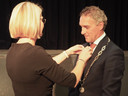 Hans Teunissen krijgt de ambtsketen omgehangen door zijn vrouw Anne-Marie.