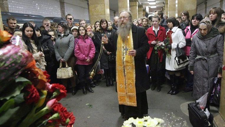 Een geestelijke van de Russisch-orthodoxe kerk houdt een herdenkingsdienst voor de slachtoffers van de aanslagen in het metrostation Park Koeltoeri. Foto EPA Beeld