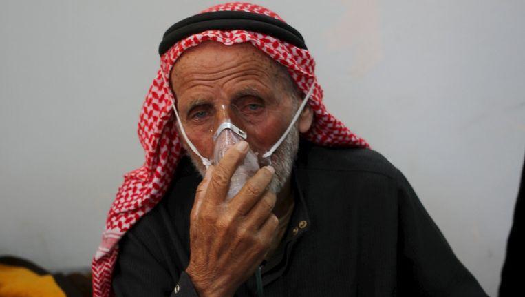 Een man ademt door een zuurstofmasker na een gifgasaanval in Idlib. Beeld Reuters