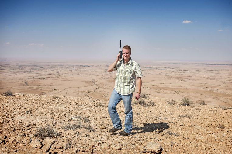 Remco Andersen probeert met een satelliettelefoon contact te krijgen met de redactie in Amsterdam in het Libische achterland op weg naar Tripoli. Beeld Guus Dubbelman / de Volkskrant
