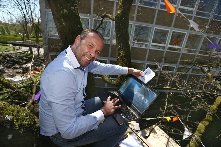 Lector Jan Van Hecke geeft les vanuit een boomhut. Met zijn laptop staat hij in verbinding met zijn studenten.