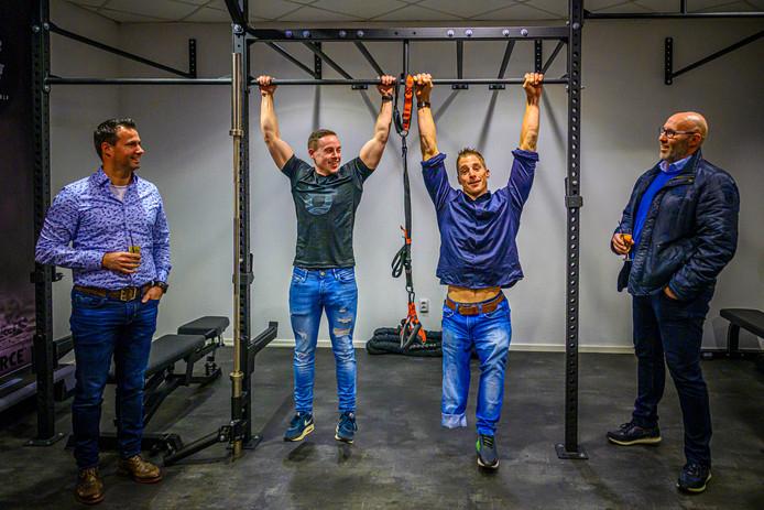 Personal trainer Quinten Aarts en paratriatleet Jetze Plat aan de rekstok in de Enforce fitnessruimte van hotel De Reiskoffer.