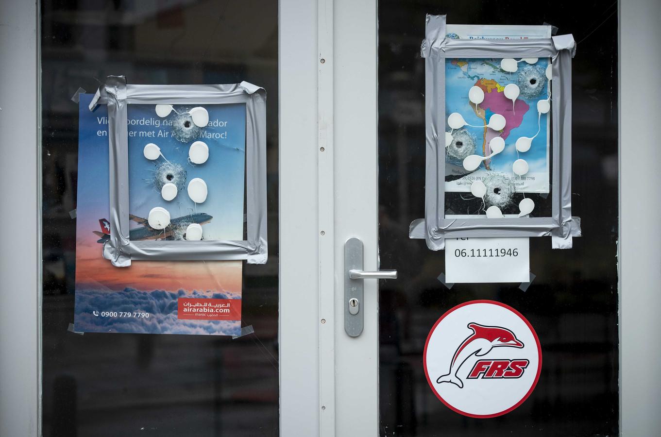 Kogelgaten in een winkelpand waarin een reisbureau is gevestigd aan de Hoefkade, dat vannacht door onbekenden in beschoten.