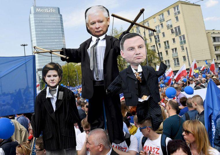 Demonstranten in Warschau beelden partijleider Jaroslaw Kaczynski uit met premier Beata Szydlo (L) en president Andrzej Duda (R) als zijn poppen, 6 mei 2017. Beeld afp