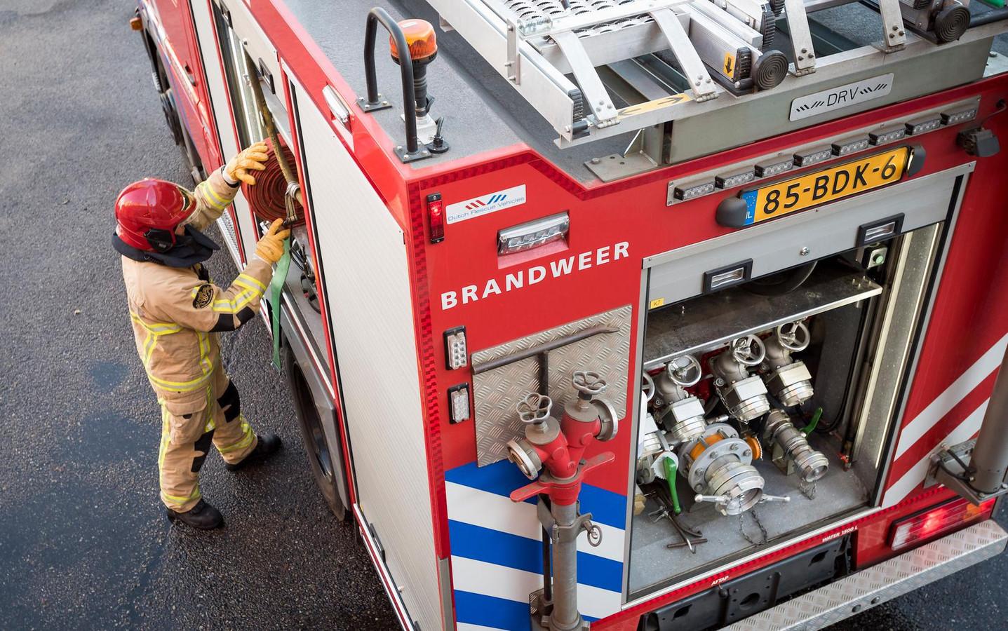 Een brandweerman pakt brandslangen uit de autospuit. Foto ter illustratie.