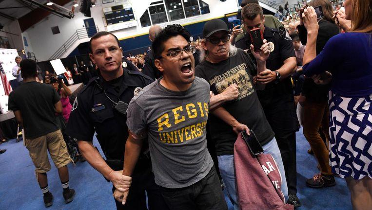 Demonstrant op Colorado Christian University wordt door de politie afgevoerd. Beeld getty