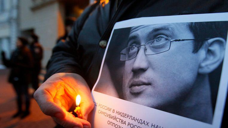 De Russische activist Aleksandr Dolmatov op een poster die door vrienden wordt vastgehouden. Beeld EPA