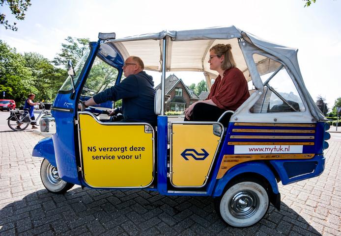 Passagiers worden van het Stationsplein-Zuid per tuktuk overgebracht naar de bussen die op de Houttuinlaan staan.