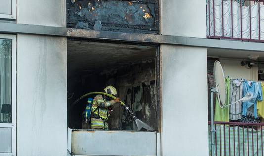 De brandweer is aan het nablussen in de uitgebrande flatwoning.