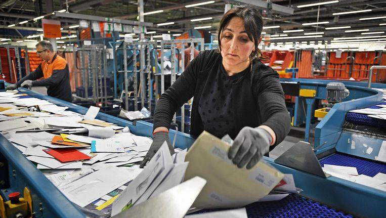 Een medewerker van PostNL sorteert de post in Amsterdam Beeld Guus Dubbelman / de Volkskrant