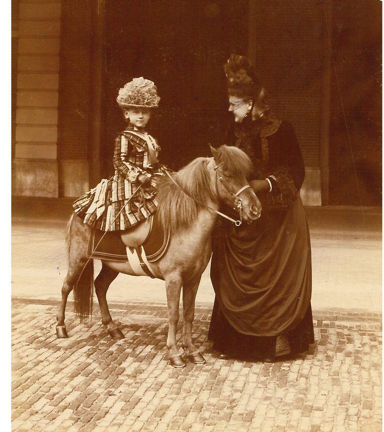 Prinses Wilhelmina op haar pony, geflankeerd door Koningin Emma in 1887. Beeld Koninklijke Verzamelingen, Den Haag