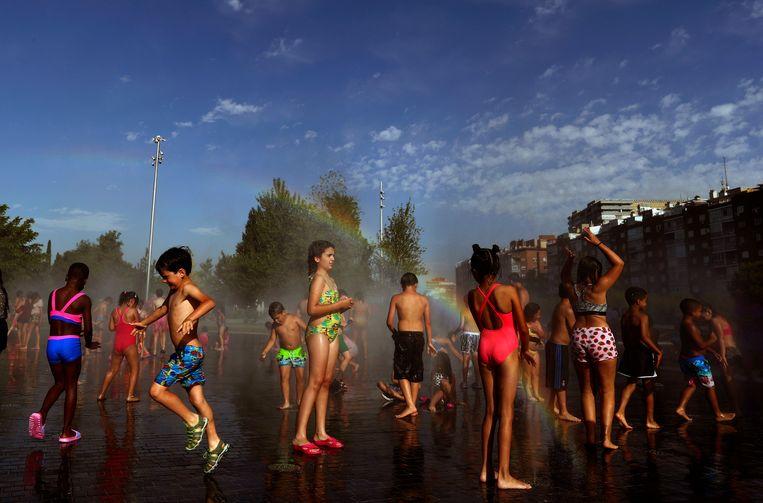 Kinderen koelen woensdag af op een 'stedelijk strand' in Madrid. Beeld AP