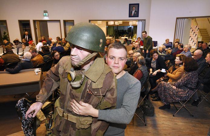 Sem Arends draagt een mannequin met geallieerde kleding naar zijn plaats tijdens zijn lezing over de Tweede Wereldoorlog.