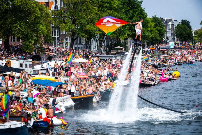Feestvierende toeschouwers op de Amstel tijdens de botenparade.