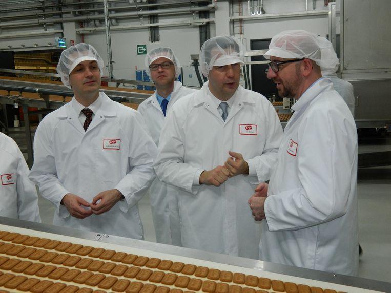 Vlnr. Alexander De Croo, burgemeester Filip Gijssels, CEO Jan Boone en premier Charles Michel moesten in de fabriek allemaal een witte jas en muts opzetten.