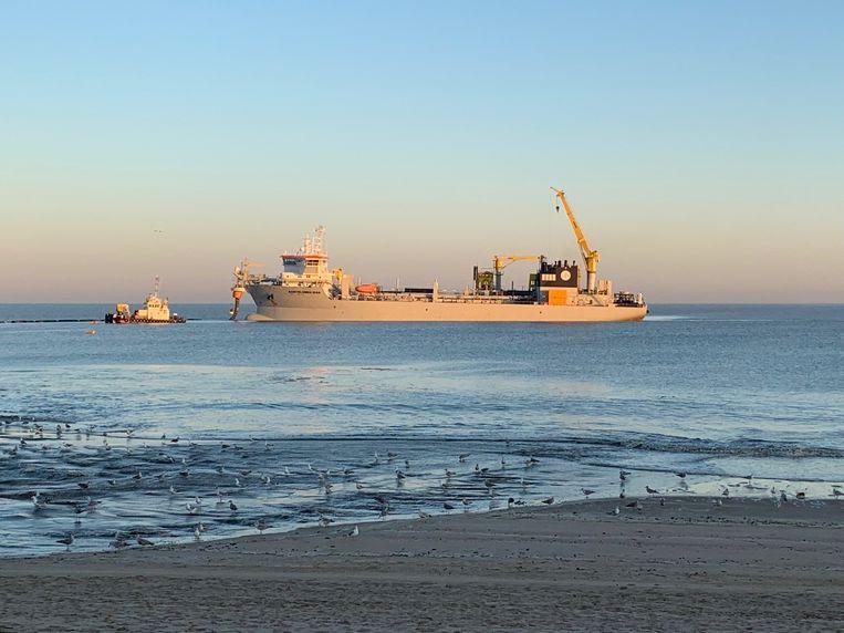 Het zand wordt via persleidingen op het strand gespoten.