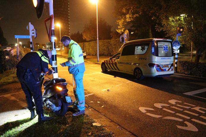 Een agent en een ambulancebroeder checken de schade aan de scooter.