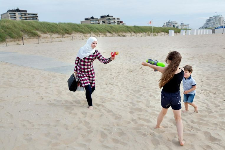 Amneh op het strand spelend met Laian. Beeld Inge van Mill