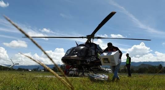 Een helikopter brengt stembiljetten naar Papoea. Elders komen ze per wagen, boot of te paard. Dozen en nog eens dozen vol.