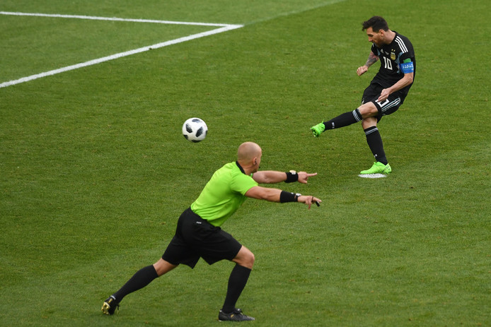 Lionel Messi neemt zijn penalty tegen IJsland, terwijl de arbiter de spelers op afstand houdt.