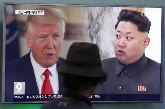 Een reiziger kijkt op een scherm in de metro van Seoel naar beelden van de twee hoofdrolspelers in de jongste crisis.