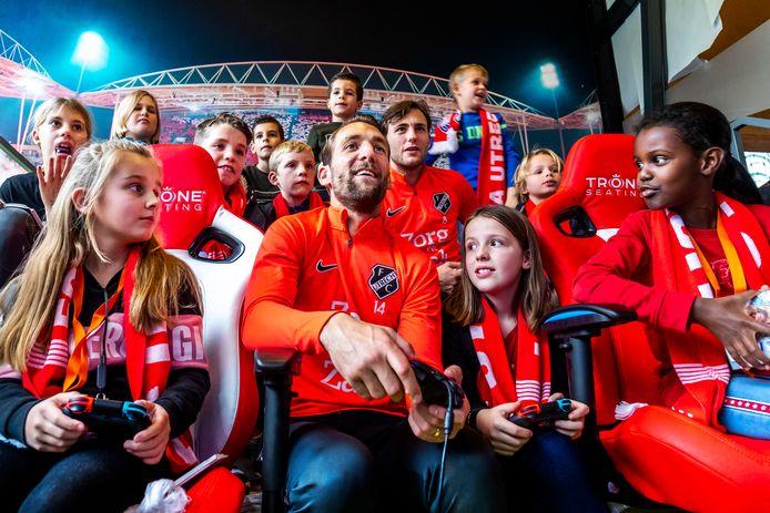 FC Utrecht-aanvoerder Willem Janssen neemt het in de 'skybox' op de spelcomputer op tegen patiëntjes van het Wilhelmina Kinderziekenhuis. Joris van Overeem geeft rugdekking.