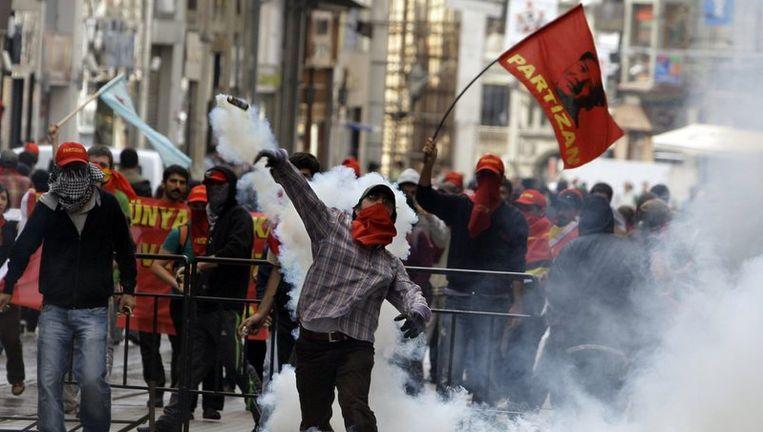 Sommige betogers zwaaiden met rode vlaggen en droegen spandoeken met leuzen als 'jullie democratie is dictatuur, jullie economie is slavernij'. Foto AP Beeld
