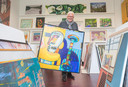 Diederick Spaas, vrijwilliger van Kunstuitleen De Bevelanden in Goes met een werk van Henk Vierveijzer.
