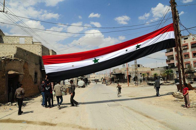 Een Syrische vlag in de stad Douma, die onlangs heroverd werd door regeringstroepen op rebellen na een wekenlange belegering. Beeld AFP