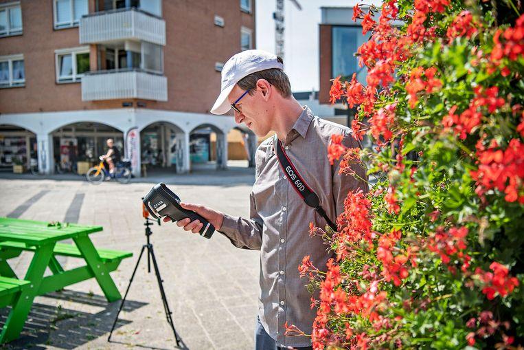 Een medewerker van de Hogeschool Amsterdam meet de hitte op het Osdorperplein voor het Cool Towns Project Beeld Guus Dubbelman / de Volkskrant