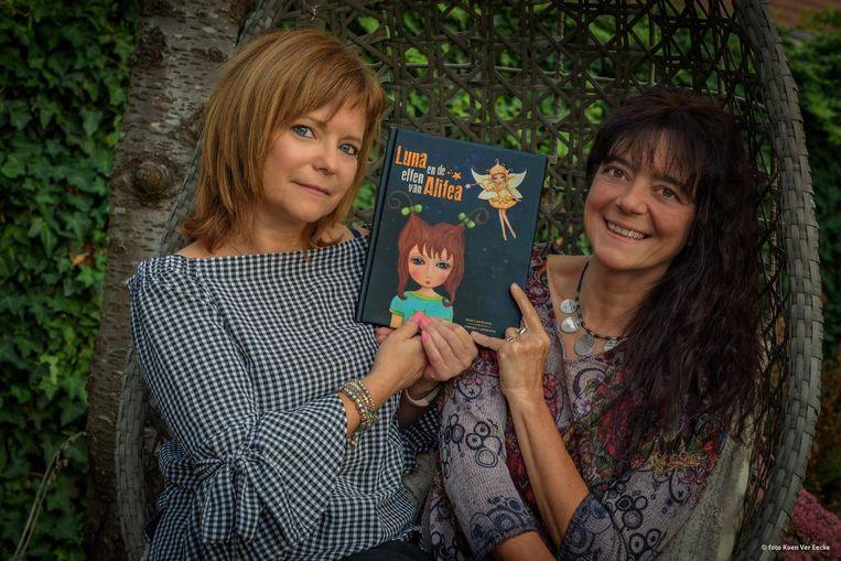 Zussen Cristel en Inge met hun kinderboek 'De elfen van Alidea'.