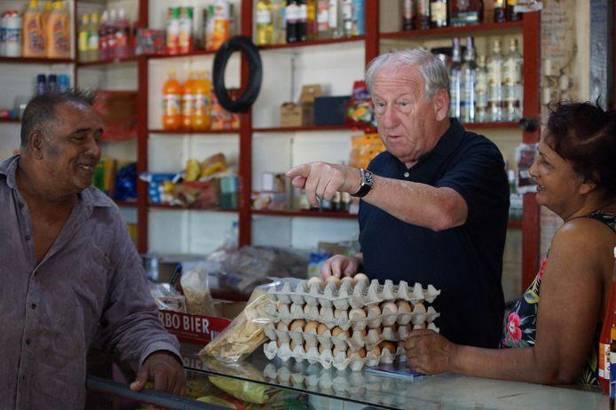 Gerard van den Tweel in een kruidenierszaakje op een plantage. Het winkeltje wordt bestierd door Robbie, een afnemer van de producten van Van der Tweel.