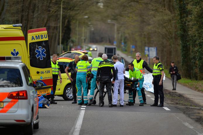 Ambulancemedewerkers en politie ontfermen zich over de zwaargewonde motorrijder, die later op de middag zou overlijden.