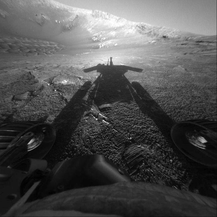 De schaduw van Opportunity glijdt in 2004 over het buitenaardse landschap van Mars. Beeld Nasa