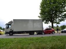 Auto klem onder vrachtwagen, bestuurster gewond
