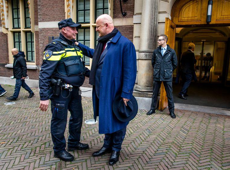 Ferdinand Grapperhaus van Justitie en Veiligheid (CDA) in gesprek met een agent op het Binnenhof. Beeld ANP
