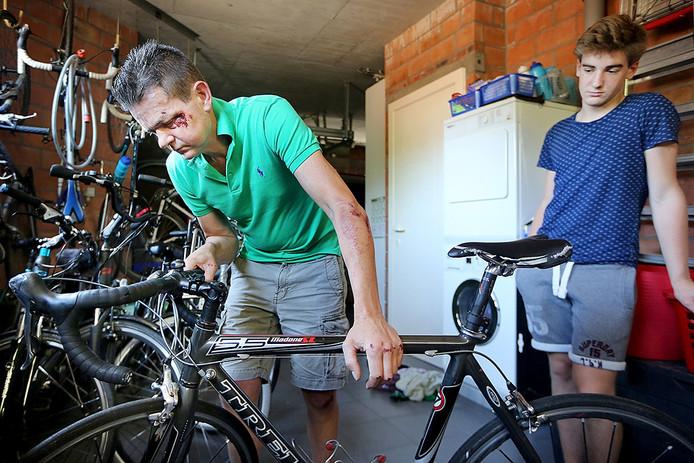 Wieleenner Marc Kenis (49) bekijkt de schade aan zijn fiets (let op het verschil in richting tussen voorwiel en stuur) nadat hij afgelopen zondag werd aangereden. rechts zoon Brend die gelukkig ongedeerd bleef.