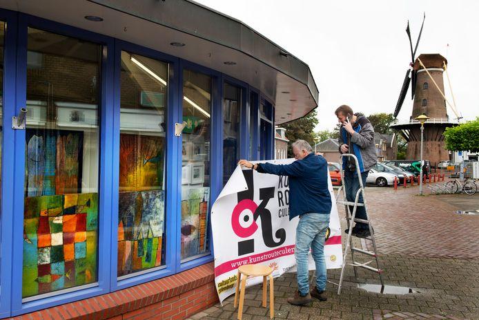 Kunstenaar Henk van der Gronde (links) hangt samen met Kees Schouten een affiche op voor de vijfde editie van Kunstroute Culemborg.