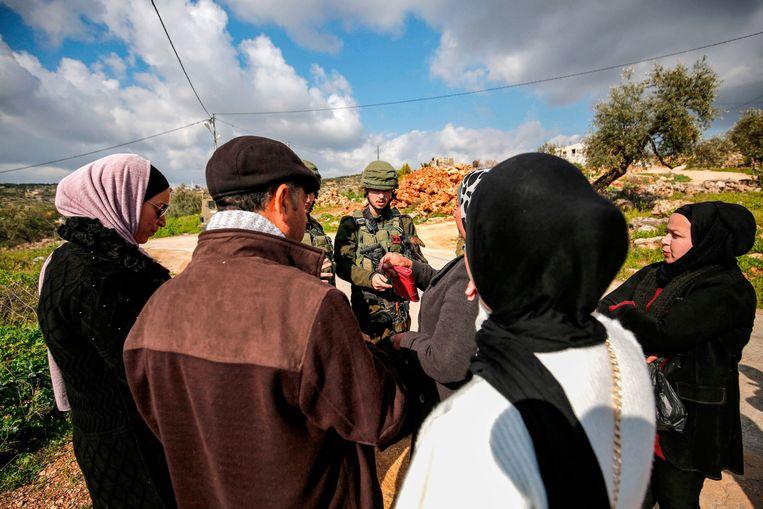 Palestijnen spreken met Israëlische militairen aan een checkpoint in Bruqin, in bezet gebied. Beeld AFP