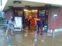 Personeel van het Okay-filiaal in de Polbroek werkt het water naar buiten.